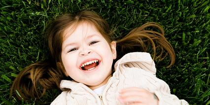 Happy toddler laying on green grass during the summer