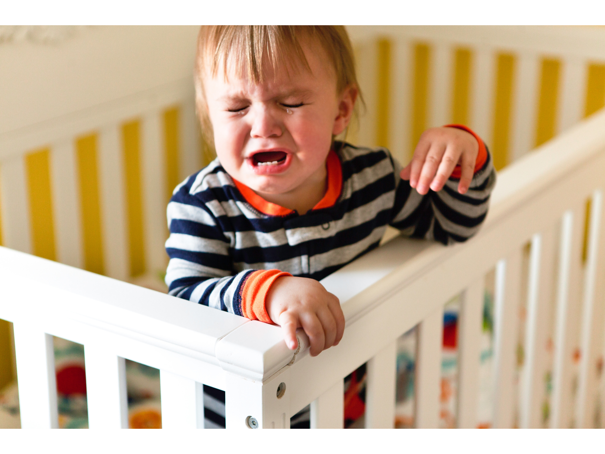 Toddler holding onto the edge of his cot, while throwing a tantrum