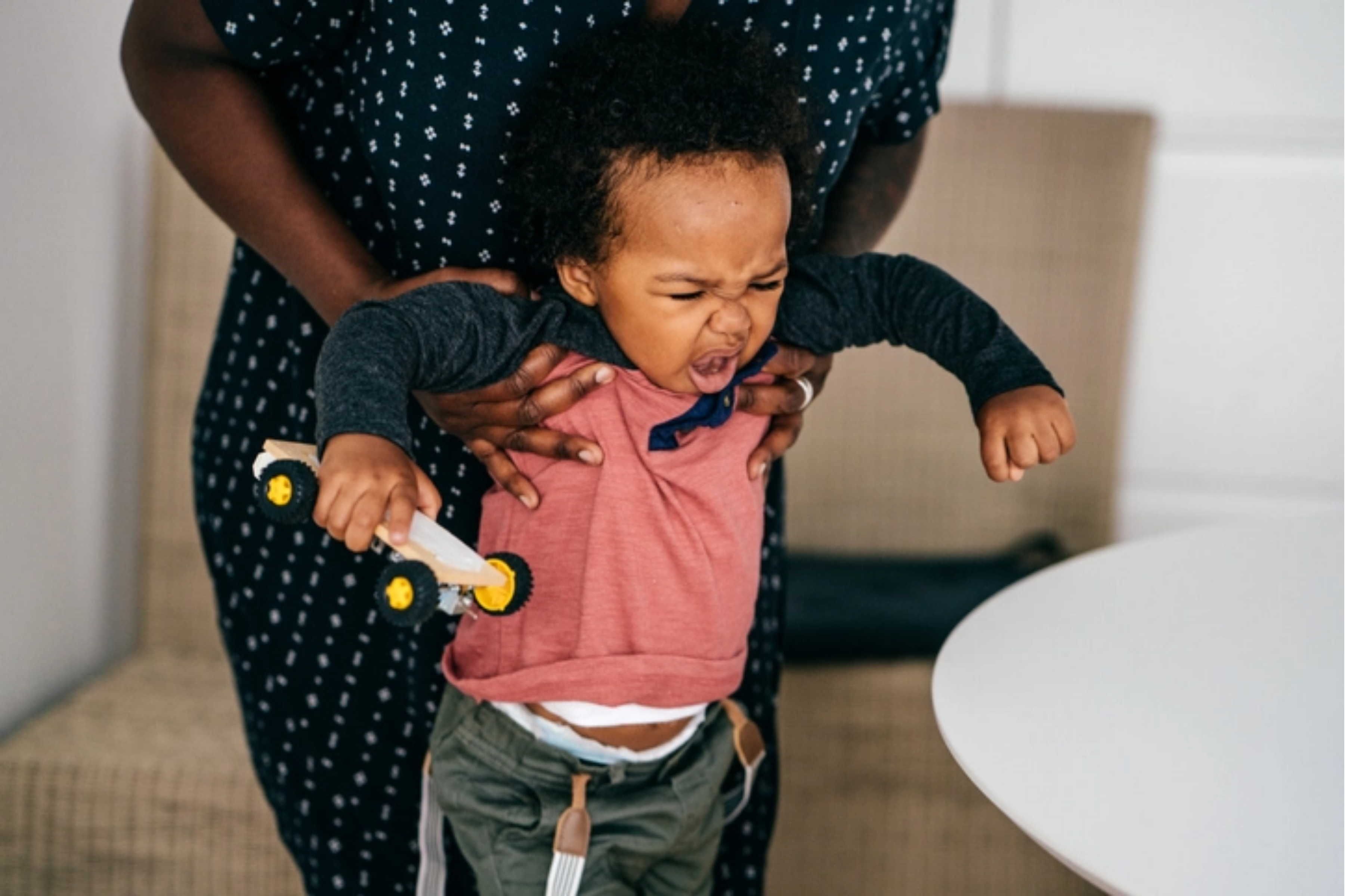Toddler wearing a pink and navy top throwing a tantrum in the dining room while her parent is holding her under her arms