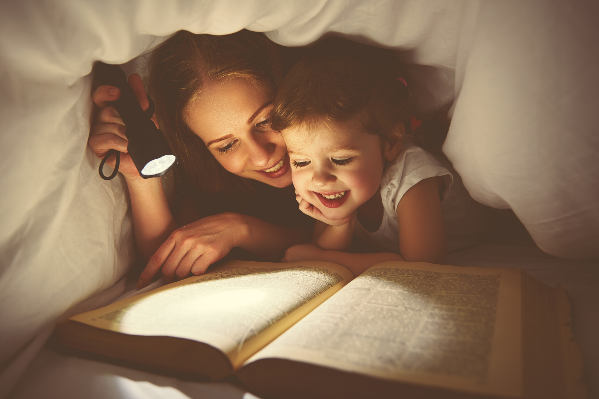 Mum with a torch reading to her child underneath bed covers