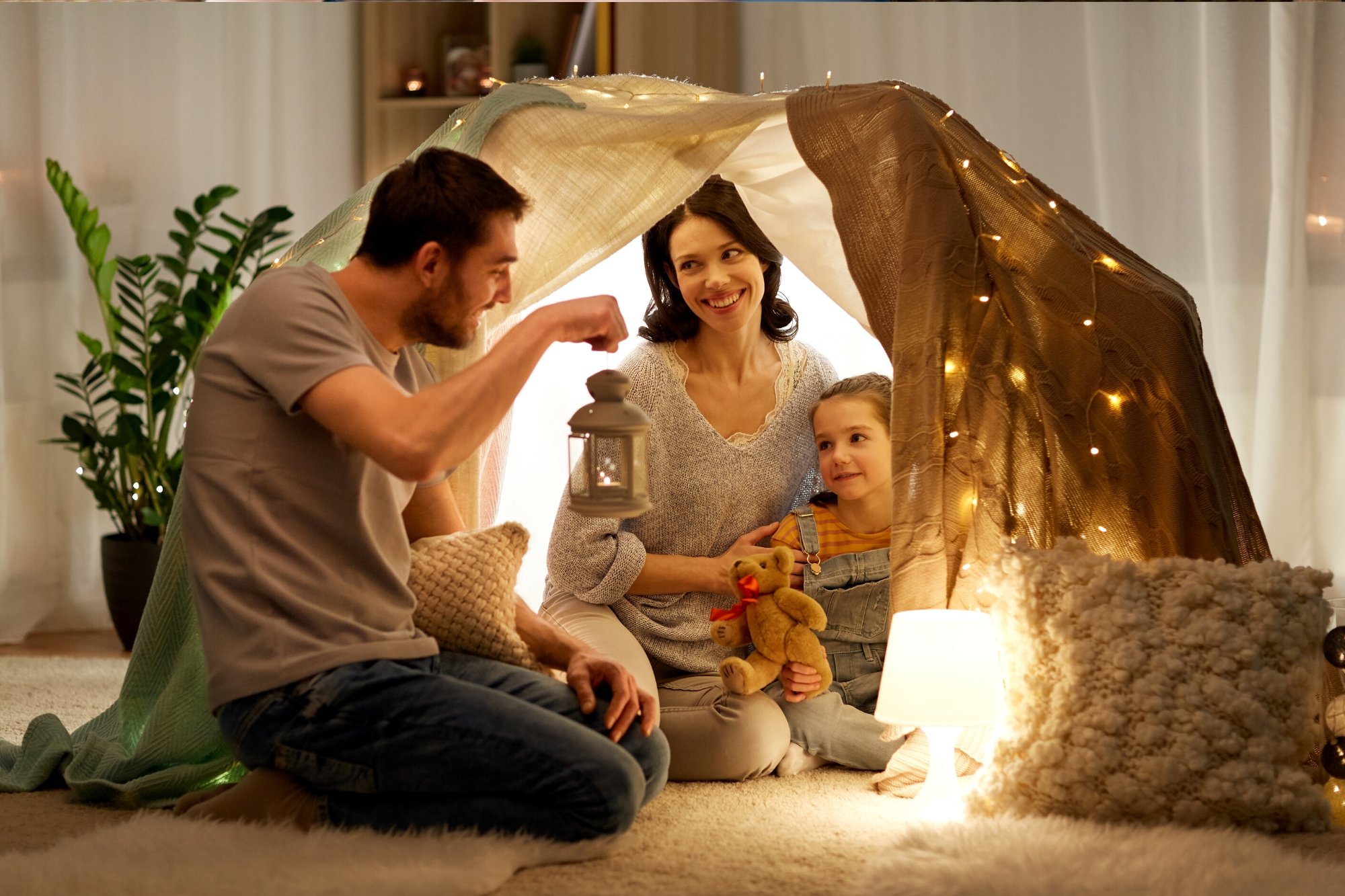 Mother and Father playing with their child in an indoor fabric lit up tent