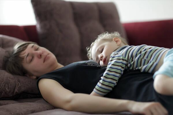Toddler and mother asleep on the sofa