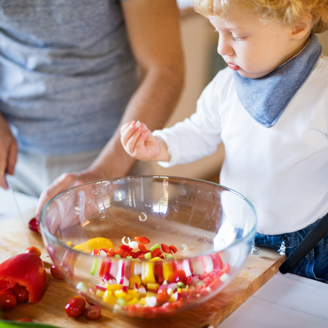 Toddler wearing a white top and blue handkerchief around his neck holding some chopped peppers in the kitchen
