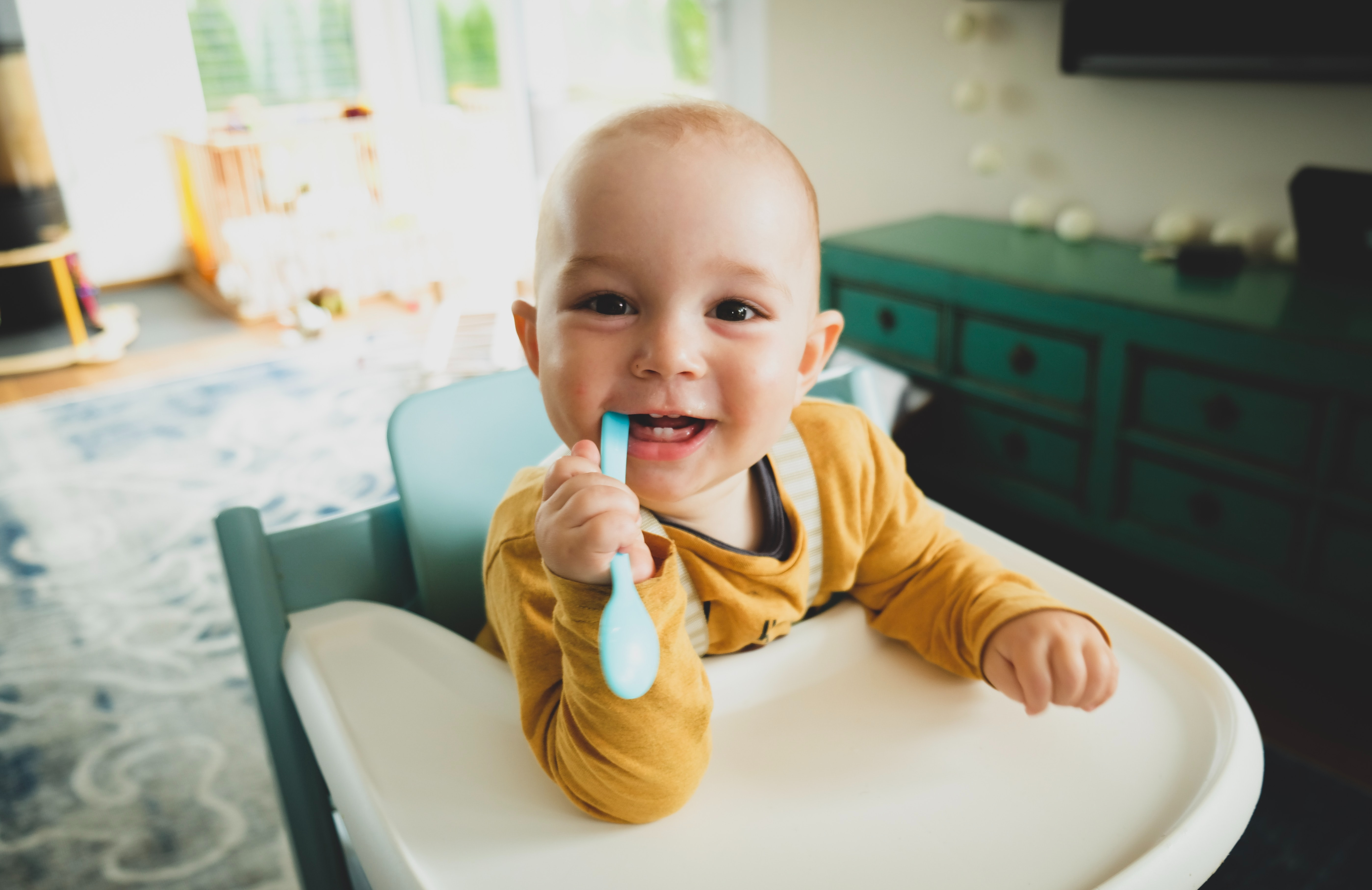 toddler sat in a high-chair smiling and biting on a plastic spoon