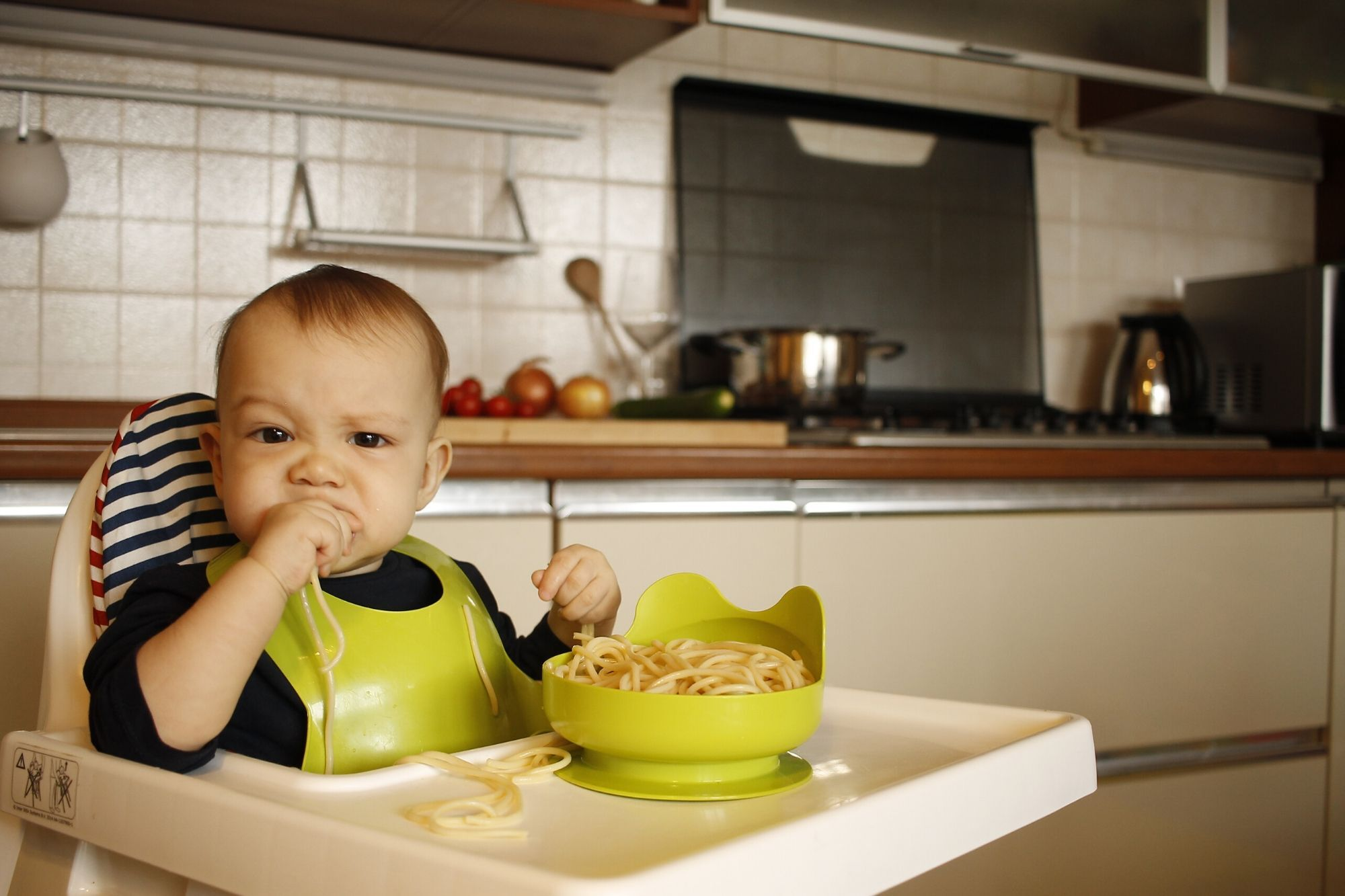 Toddler in a highchair eating pasta from a green bowl