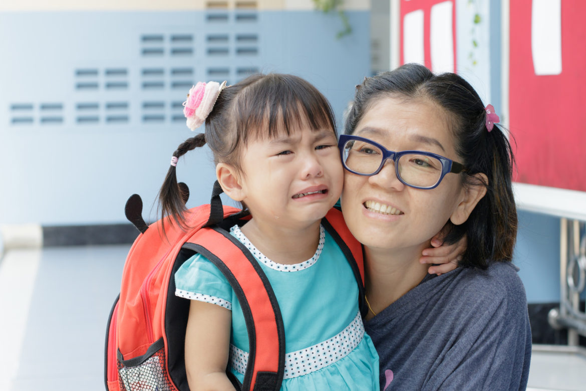 A child crying at the school gates or walking with mother