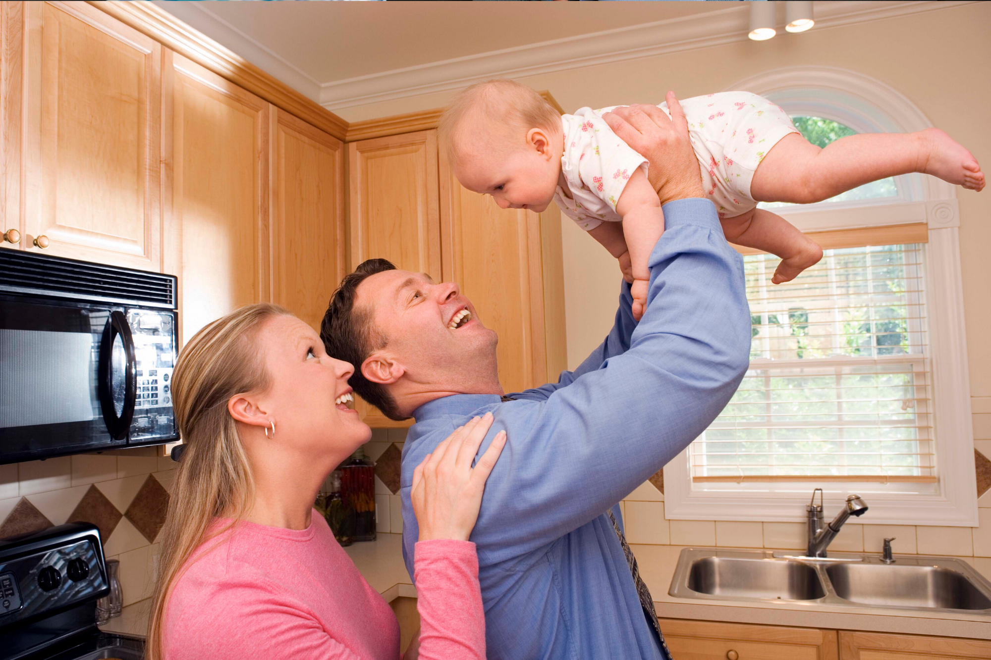 Parents engaging with baby in the kitchen