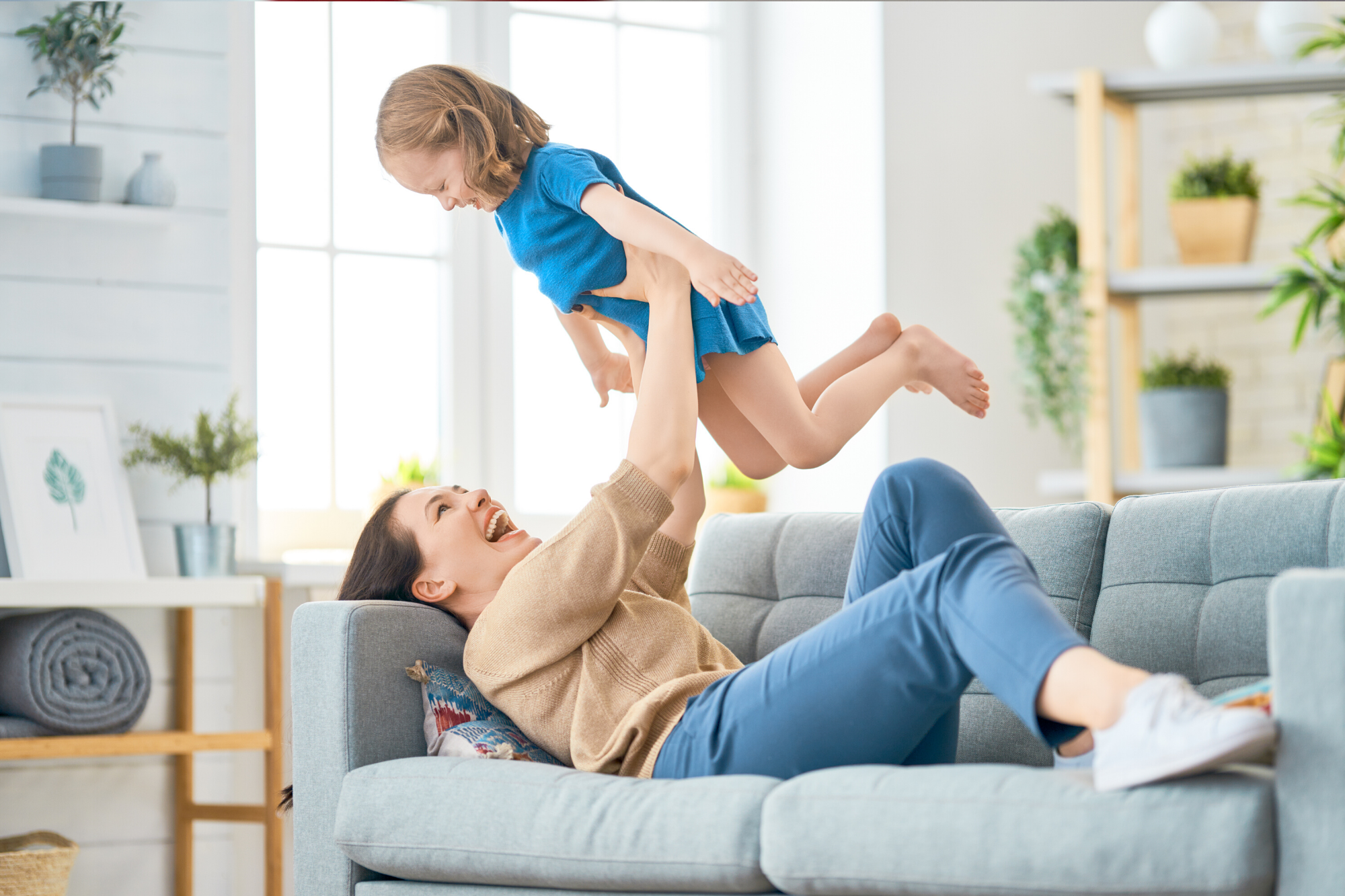Child in a blue t-shirt and shorts being held up in the air by his mum