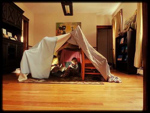 Siblings sitting inside a homemade fort in their living room, reading with a torch