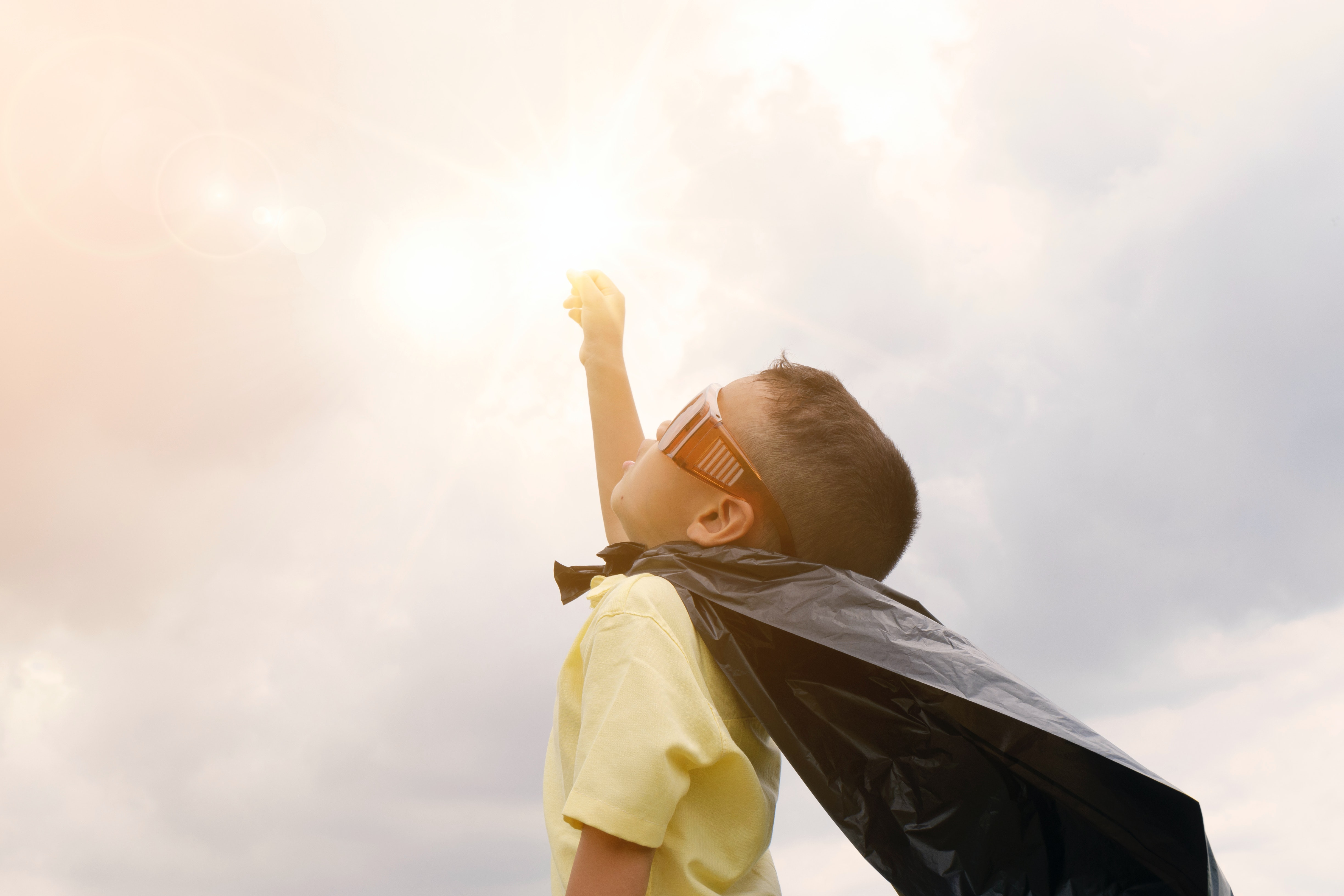 Toddler pointing to the sky, wearing a cape and sunglasses pretending to be a superhero