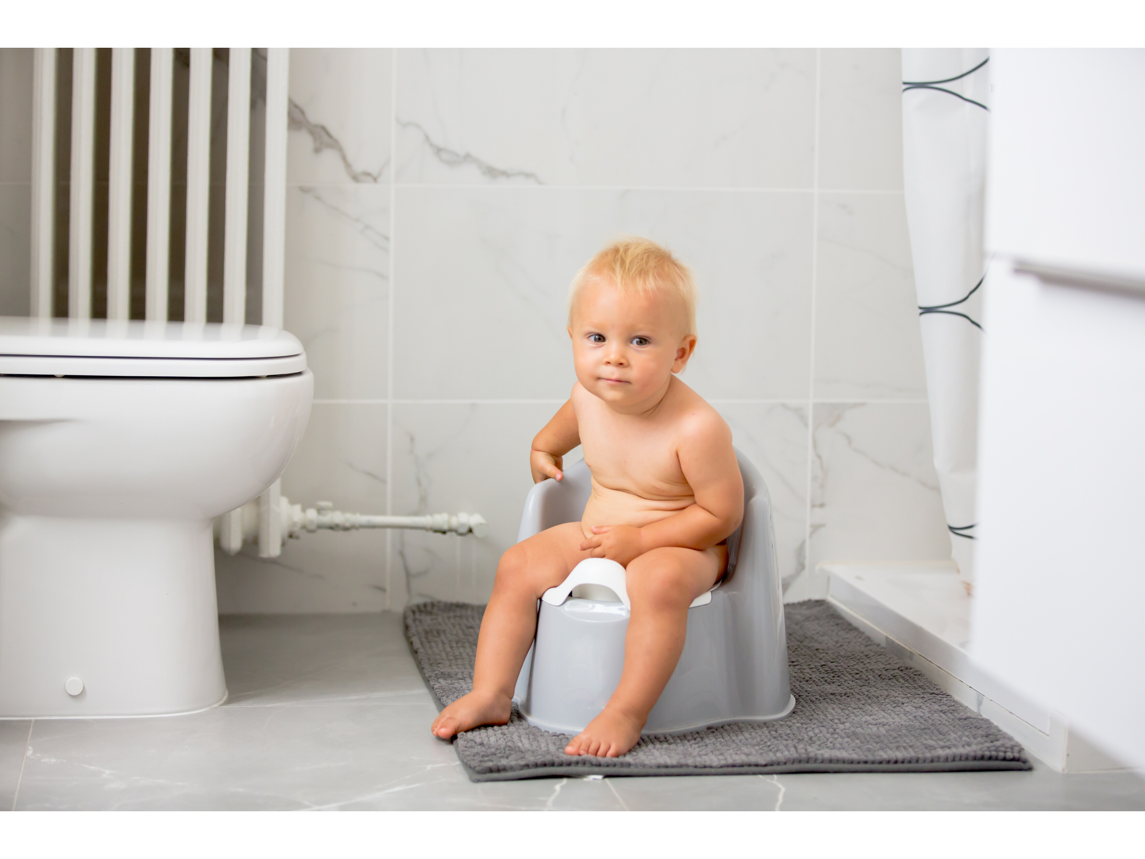 Child sitting on a potty in the bathroom