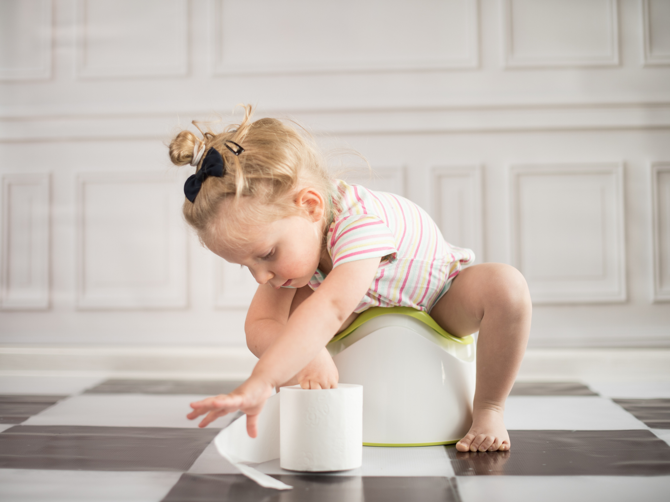 Toddler sitting on a potty and reaching for toilet paper