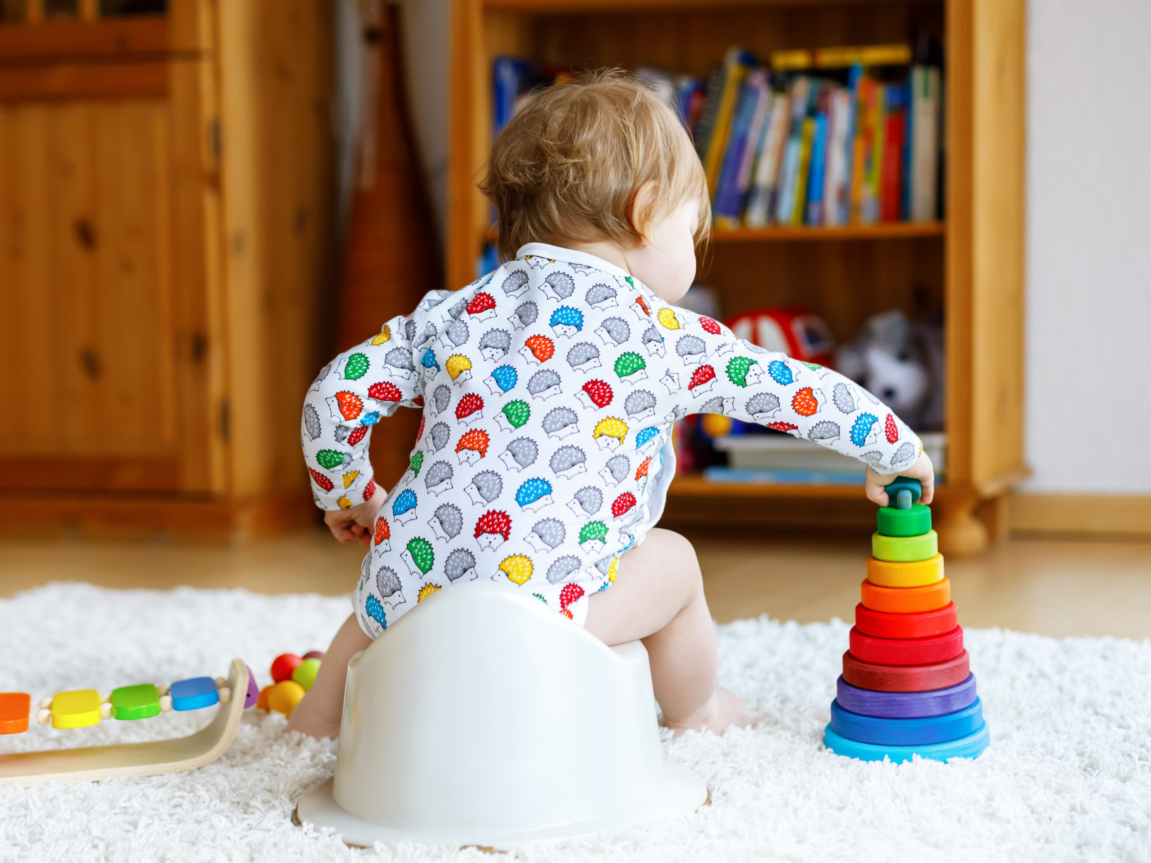 Toddler potty training and playing with toys in the living room