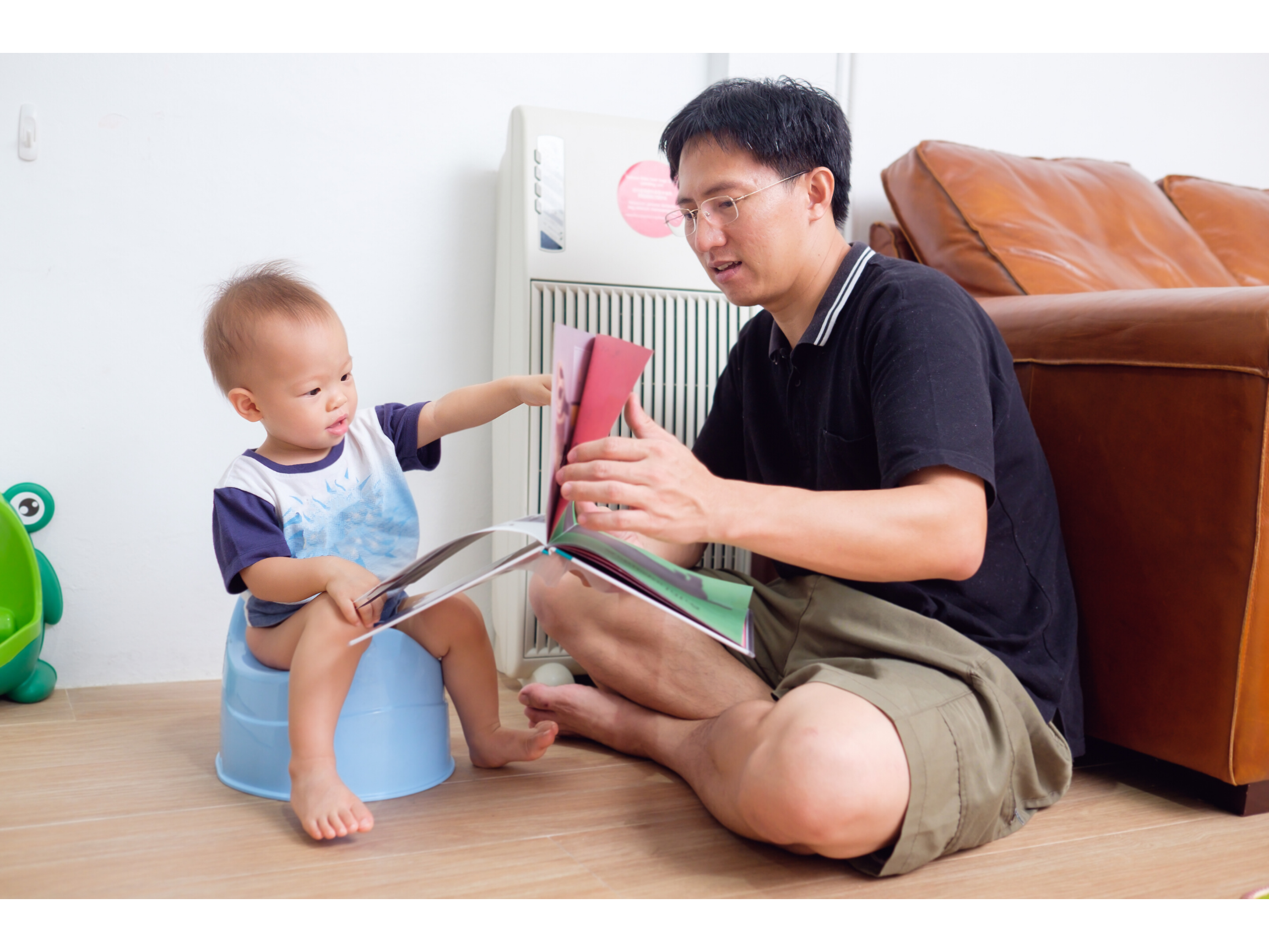 Dad reads to his child in the living room while they start to potty train