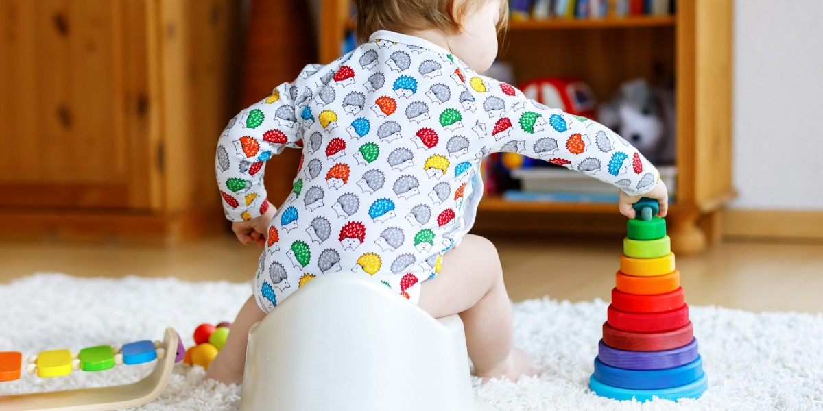 Child wearing a colourful bodysuit, potty training at home and playing with his multi-coloured stack toy
