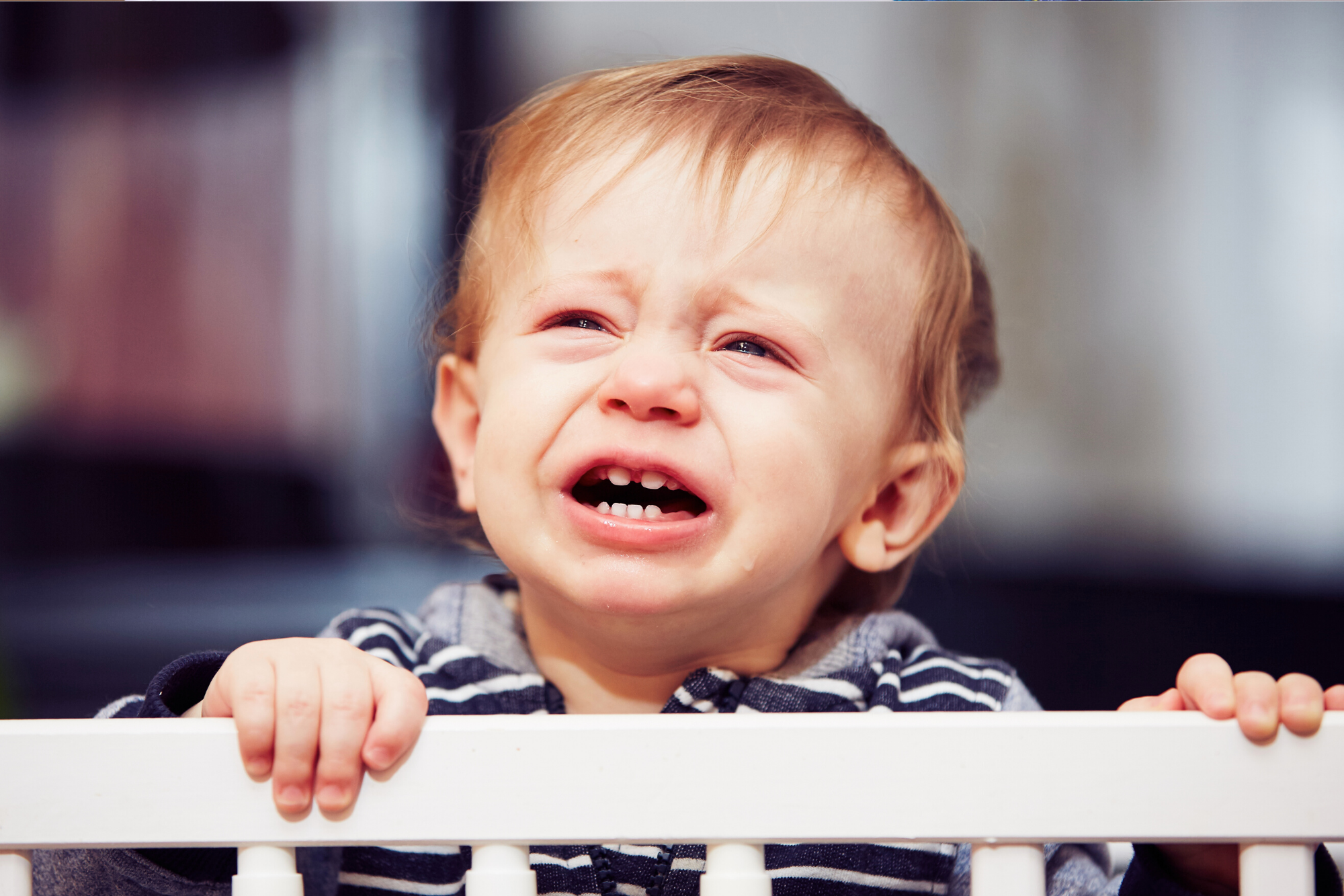 Baby boy crying while holding onto the edge of his cot