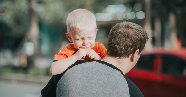 Child wearing an orange t-shirt crying while his dad holds him