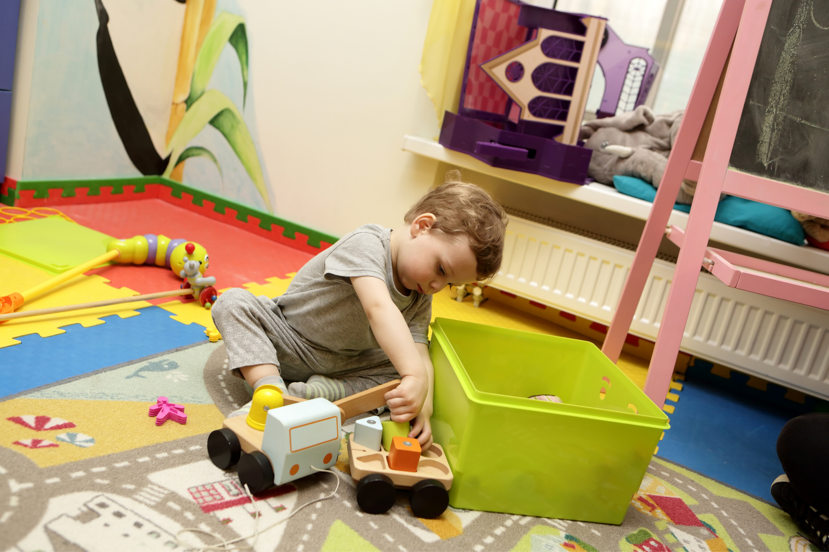 Little boy wearing a grey outfit, playing with toy cars beside a green plastic box
