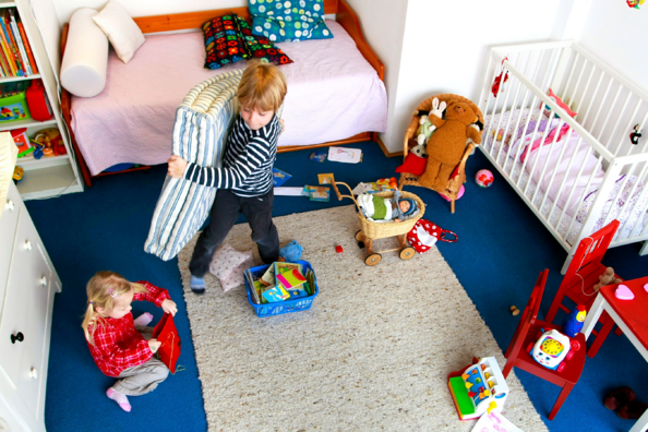Toddler helping his little sister tidy up bedding and toys in their bedroom