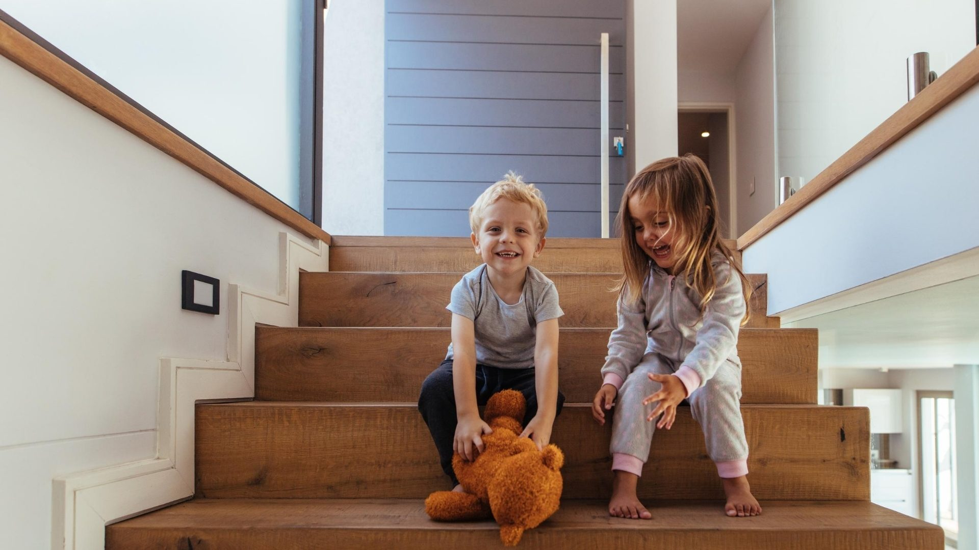 Children playing with a brown teddy bear on the stairs at home
