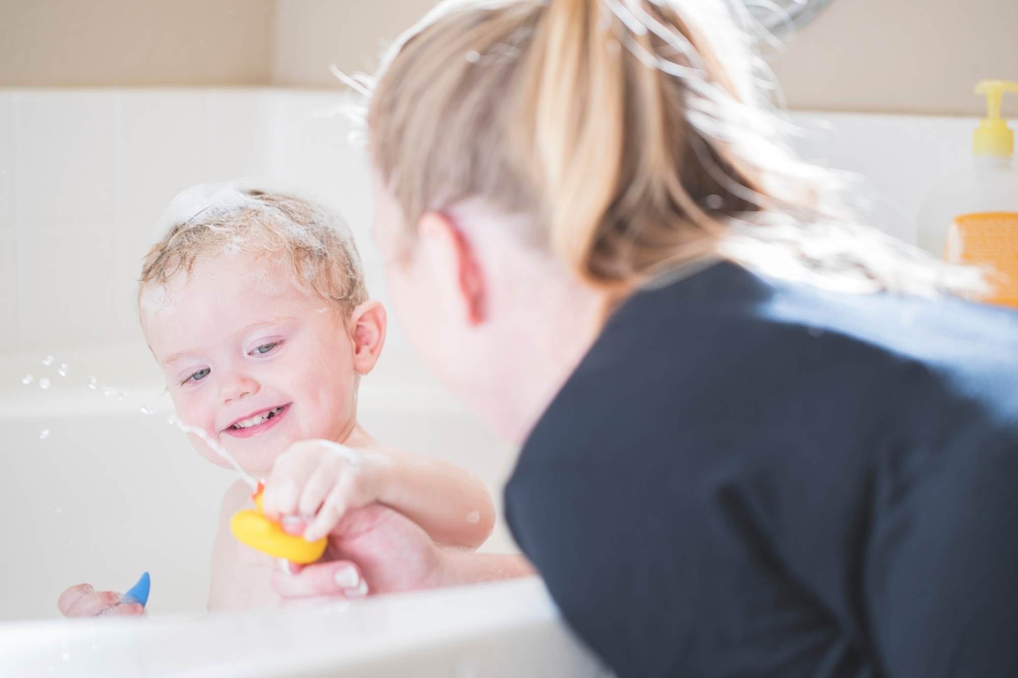 Mum playing with her preschooler and a rubber duck who is having a bath