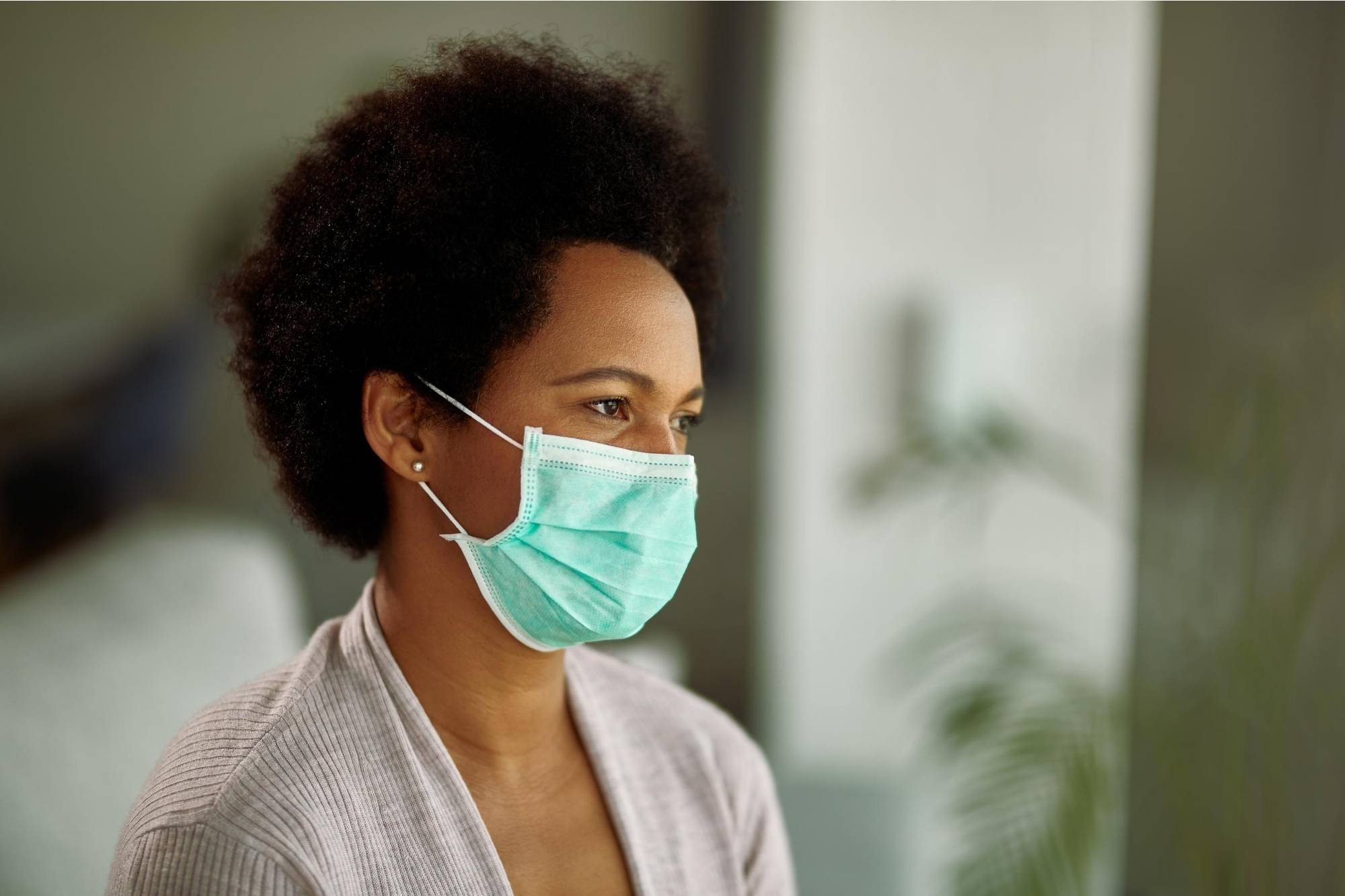 Short haired woman wearing blue face mask