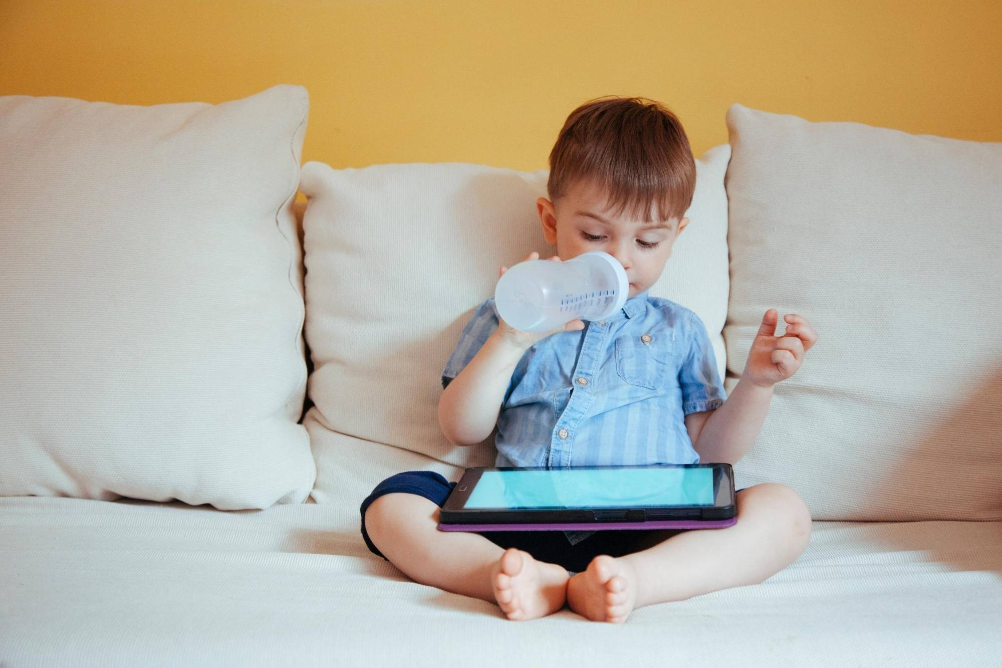 Child sitting on a white sofa looking at an iPad screen while drinking from his bottle