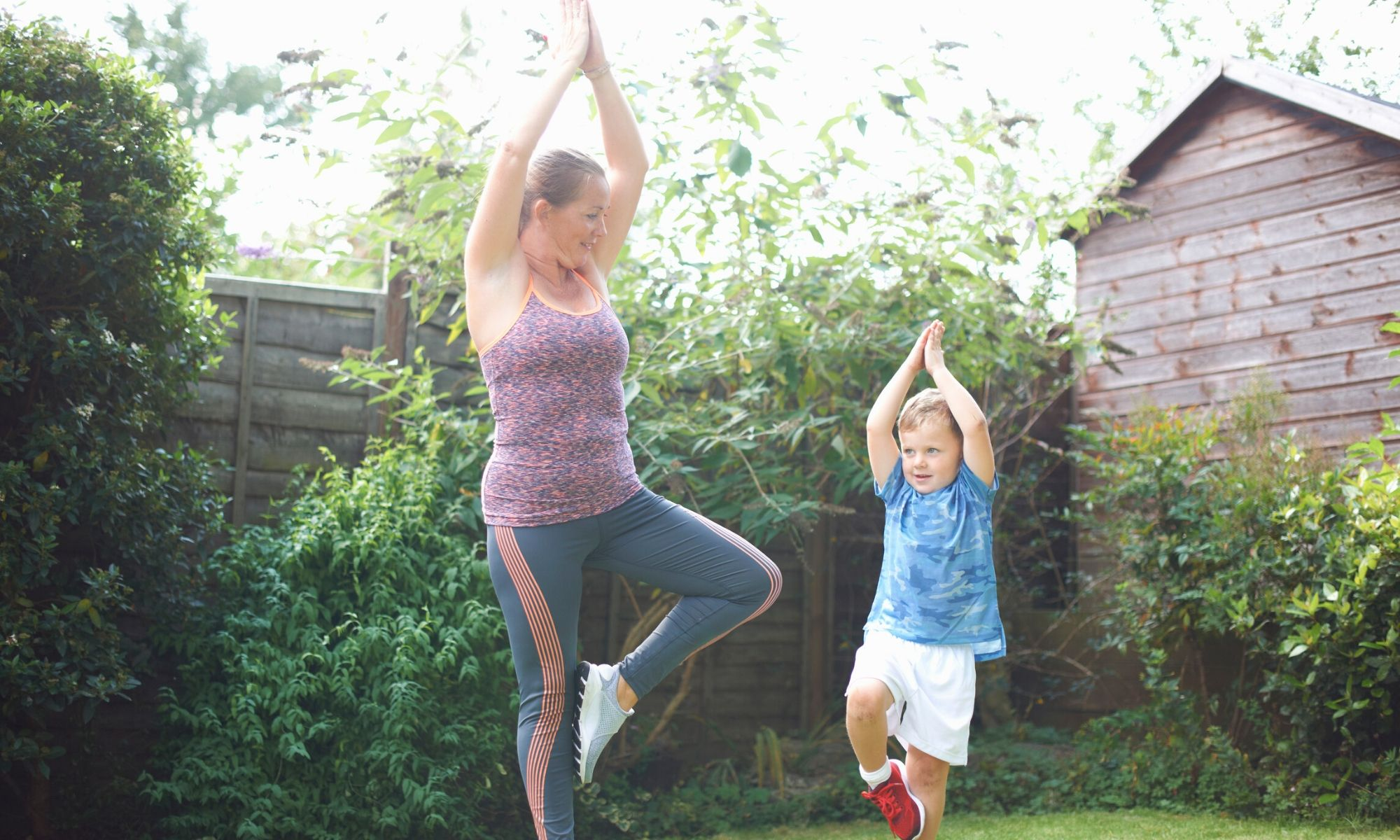 adult and child doing yoga poses outside