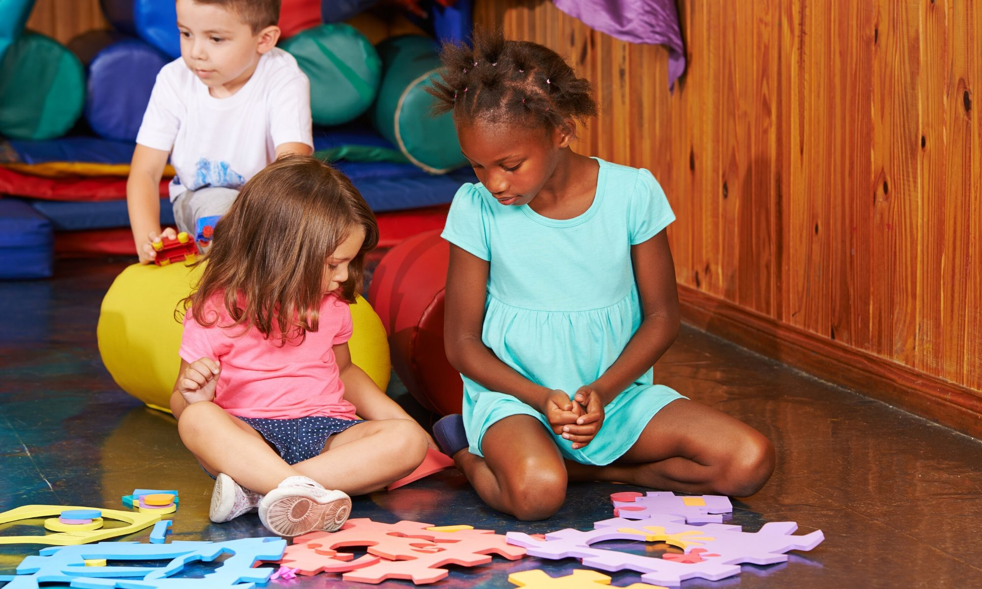 Children at their pre-school nursery sitting down to play with a colourful foam jigsaw puzzle