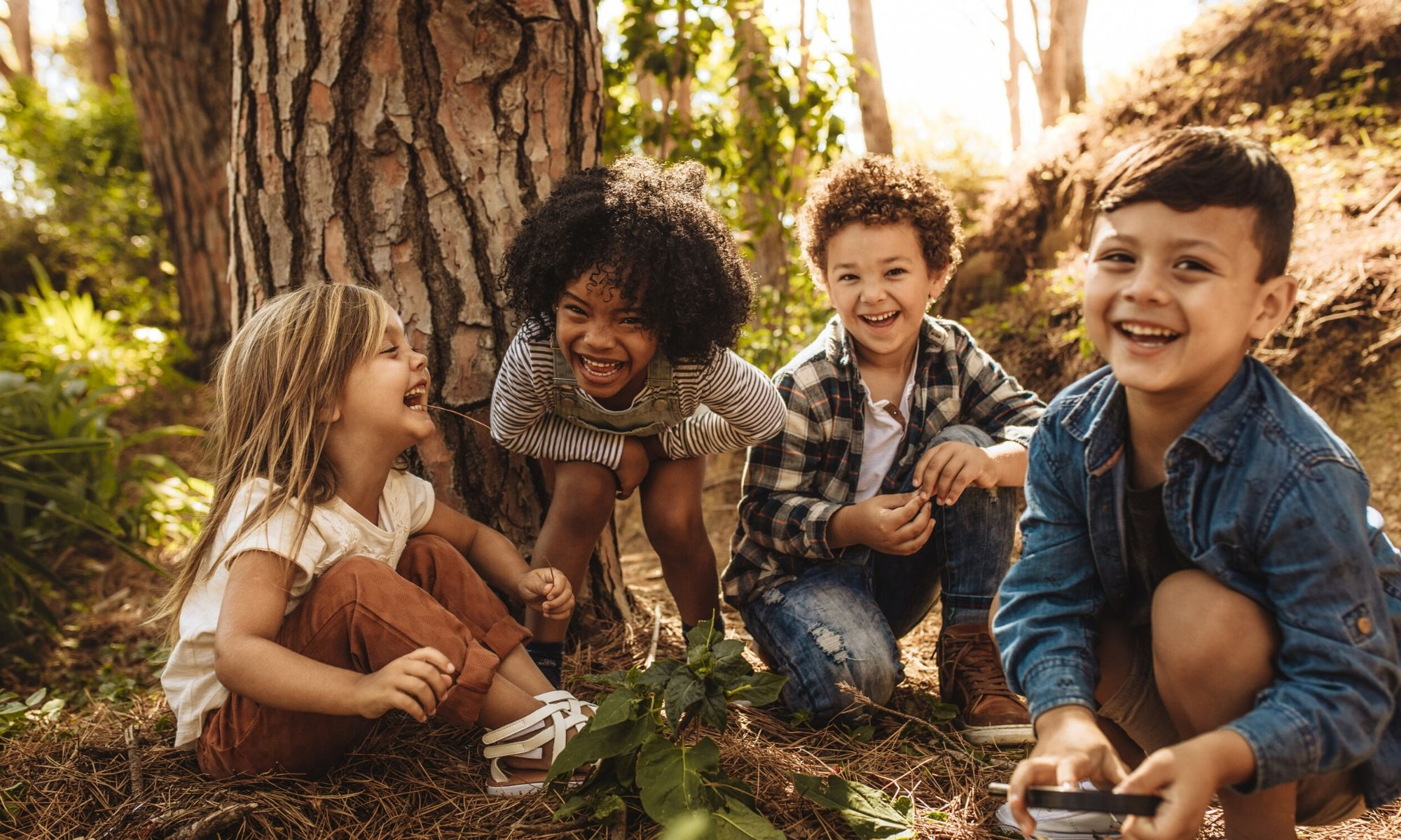 Toddlers of different races playing outdoors near a tree
