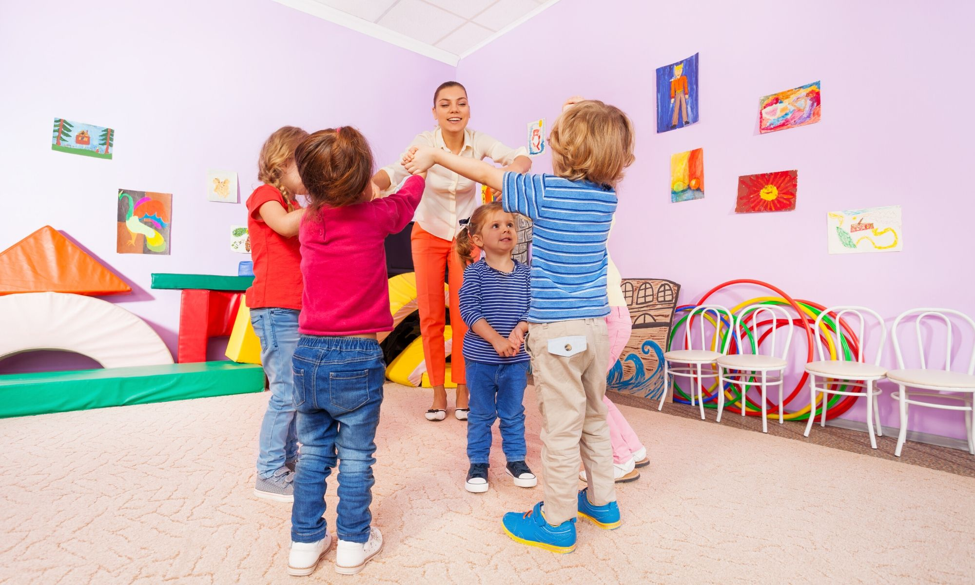 Toddlers back at their nursery playing with their friends and teacher