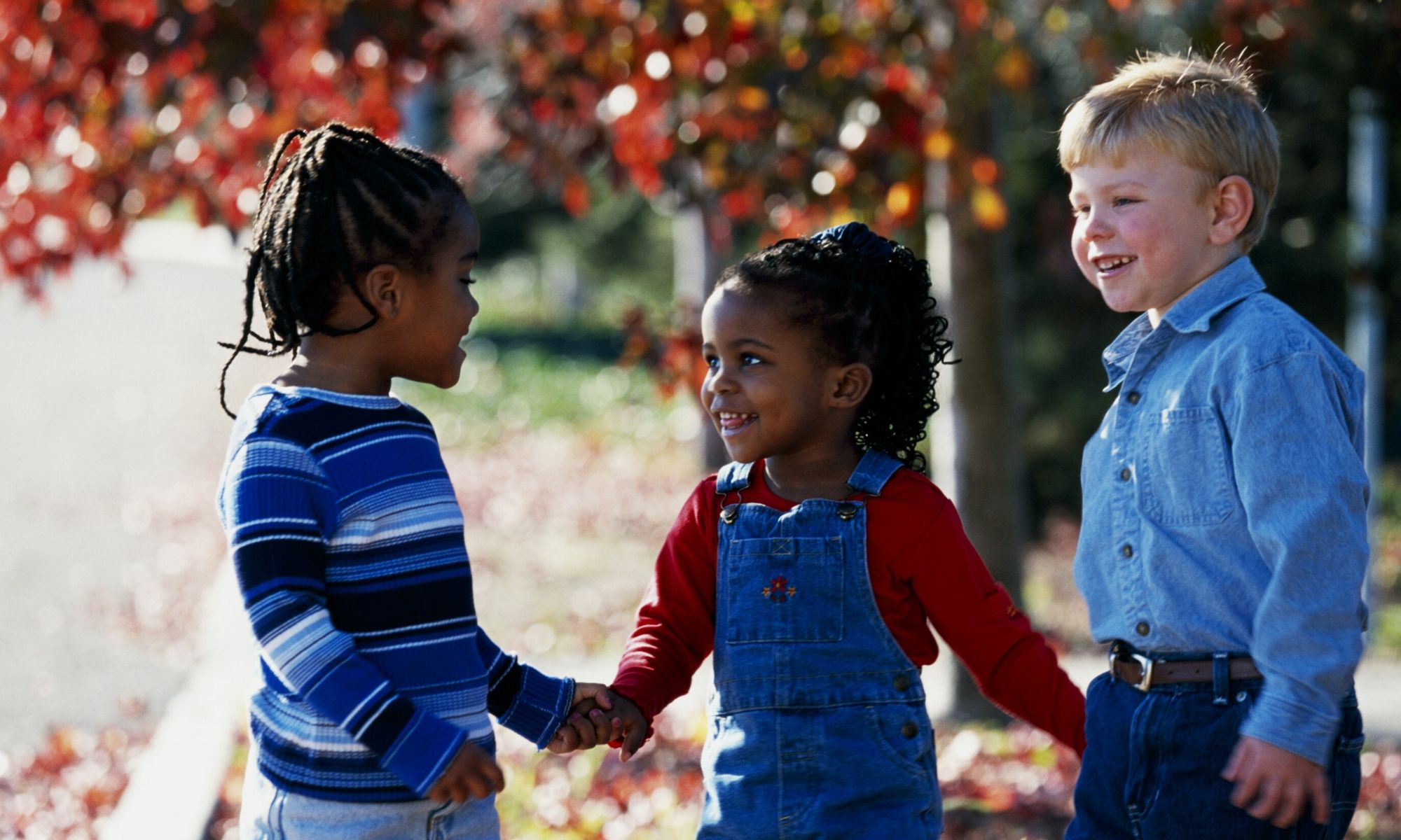 Children of different races holding hands outdoors