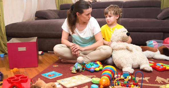 Stressed Mother sitting on the living room floor with her toddler surrounded by toys