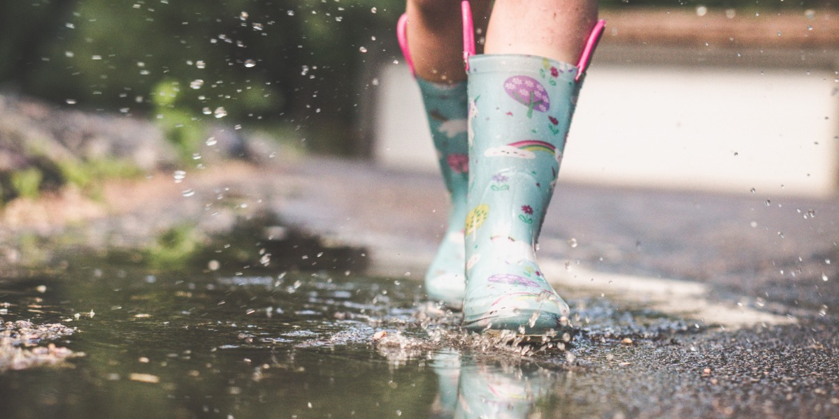 Child splashing in the puddles with wellington boots