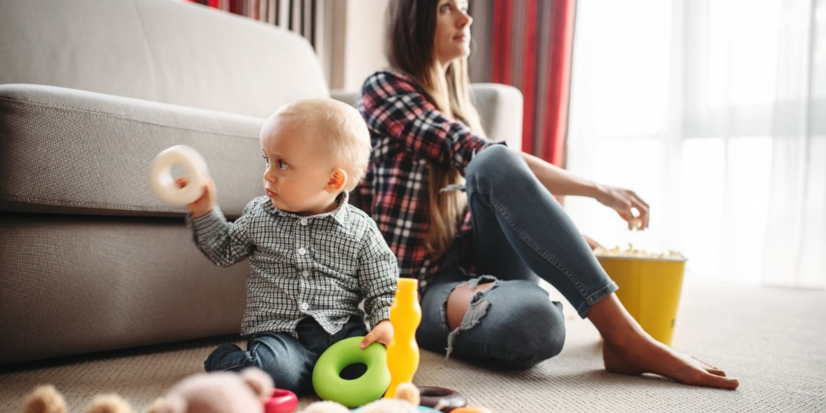 Baby in checked shirt playing with ring toys in the living room while mum takes a break