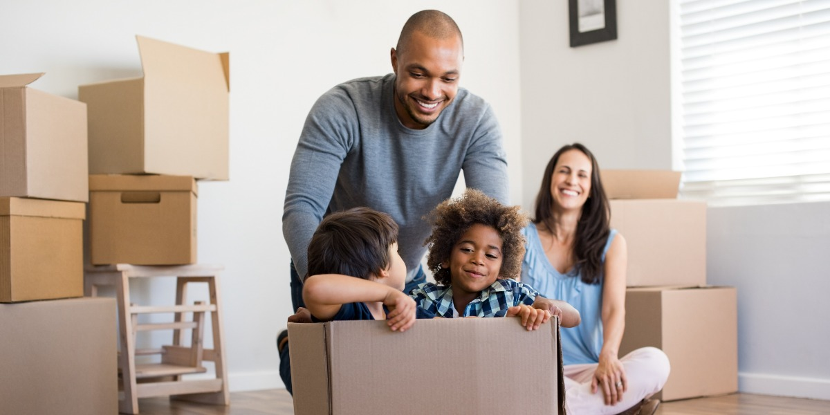 Dad and mum reconnecting with their children while they play in cardboard boxes