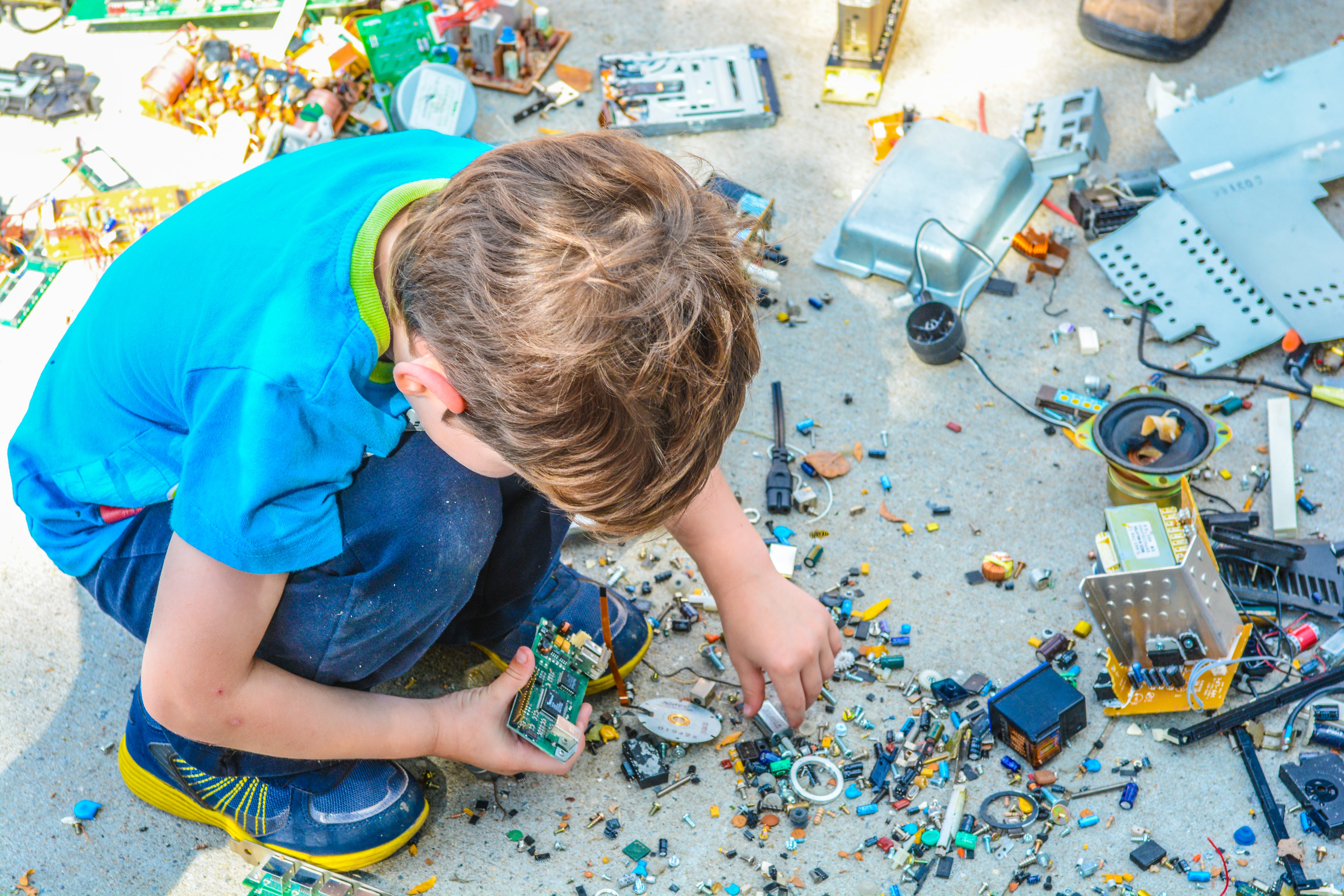 Toddler crouched and playing with recycled plastic pieces