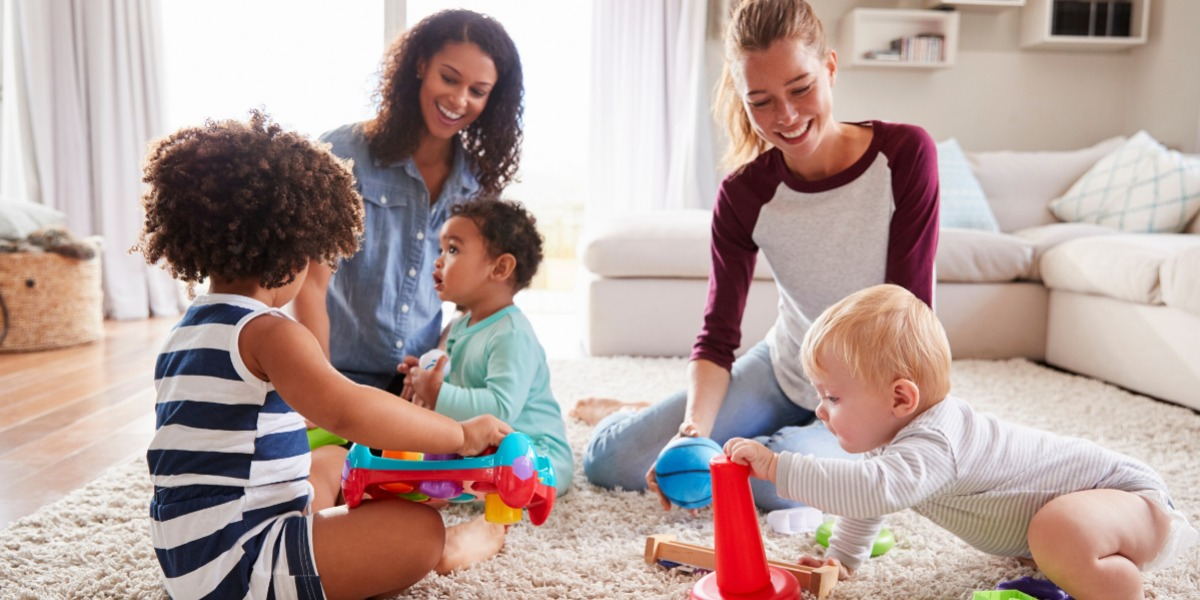 Parents supporting each other and playing with their toddlers in the sitting room