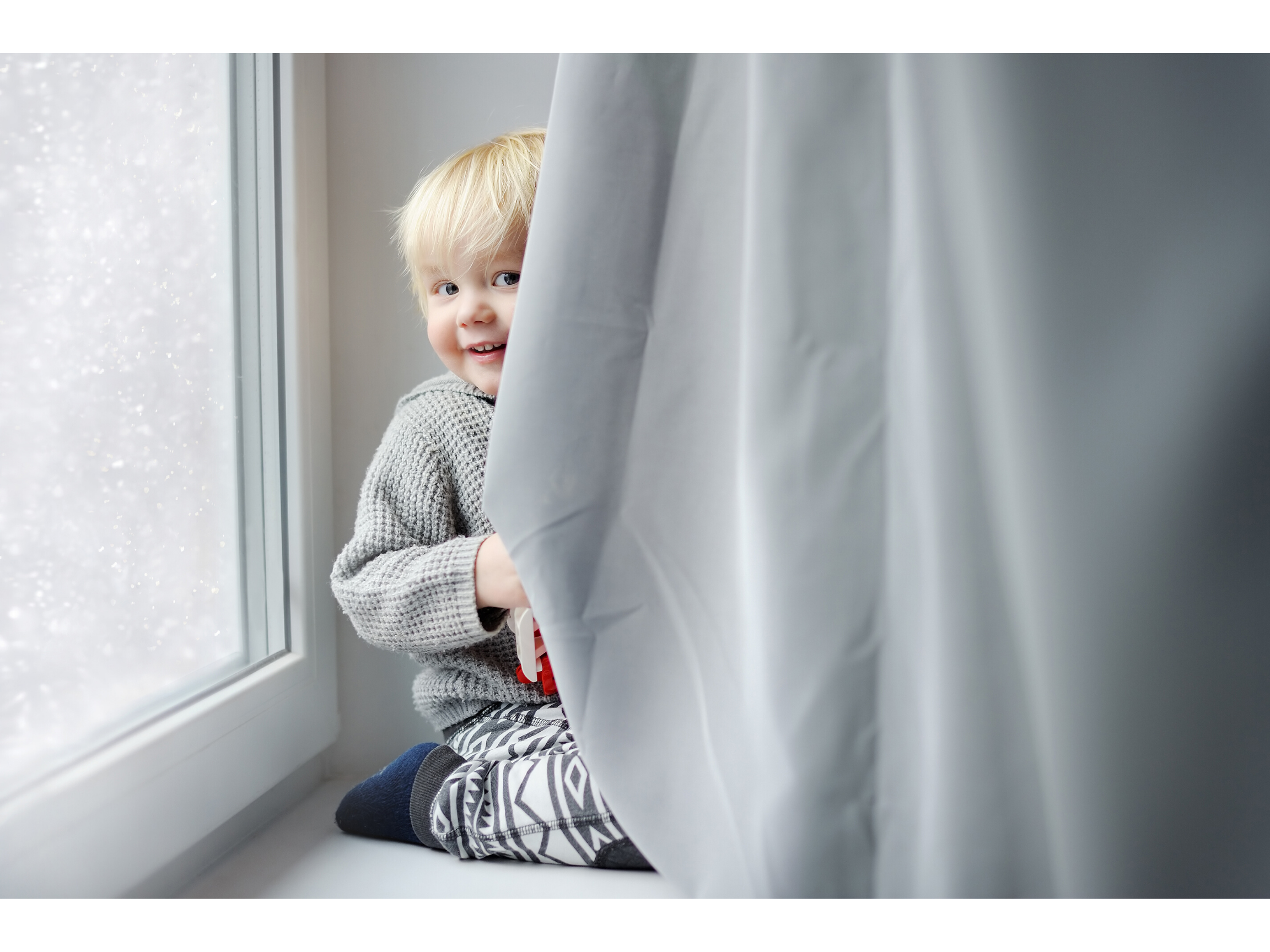 Blonde child playing behind a grey curtain preparing to return to his nursery during the COVID-19 pandemic